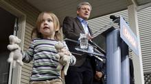 Prime Minister Stephen Harper speaks as 2.5-year-old Fiona Wellburn plays with her toys during a campaign stop in Saanich, B.C., on March 28, 2011. (THE CANADIAN PRESS)