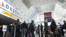 Passengers line up in the Delta terminal of LaGuardia Airport in the Queens Borough of New York, February 4, 2014. (KEITH BEDFORD/REUTERS)
