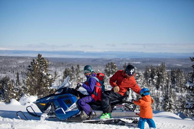 Tessa Treadway gets ready to snowmobile with her son Raffi on her back as her husband Dave Treadway loads up their other son Kasper near Tweedsmuir Ski Club.