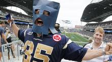 Winnipeg fan Keith Mander gets into the spirit prior to the Winnipeg Blue Bombers and Saskatchewan Roughriders CFL game in Winnipeg Sunday, September 8, 2013. The CFL announced on Thursday that the Blue Bombers will move back to the West Division for the 2014 season. (JOHN WOODS/THE CANADIAN PRESS)