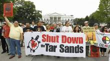 Native demonstrators hold up signs in front of the White House in Washington, Friday, Sept. 2, 2011, to protest the Keystone XL Pipeline project in the U.S., and the tar sands development in Alberta. (Luis Alvarez/AP/Luis Alvarez/AP)