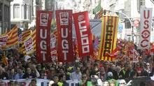 People hold banners and placards as they march during a protest against government austerity measures in Barcelona March 10, 2013. (ALBERT GEA/REUTERS)