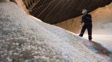 Trevor Berg holds some potash chiclets in a storage build at the Potash Cory mine near Saskatoon (Liam Richards/Photo Liam Richards)