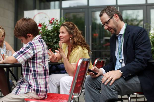 Gerald Butts, (R) advisor to Liberal leader Justin Trudeau reads his phone with Sophie Grégoire (C) and Xavier Trudeau during a reception June 17, 2014 in Ottawa.