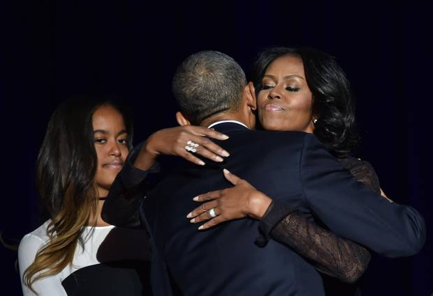 First lady Michelle Obama hugs the president as daughter Malia looks on after his speech.