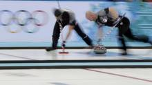 Canada's lead Ryan Harnden (L) and Canada's vice Ryan Fry sweep ahead of a stone during their men's curling semi-final game against China at the 2014 Sochi Winter Olympics in the Ice Cube Curling Center in Sochi February 19, 2014. (PHIL NOBLE/REUTERS)