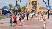 Visitors head toward the entrance of the Universal Studios Florida theme park in Orlando, Fla., April 22, 2006. (PHELAN M. EBENHACK/AP)