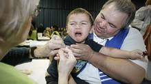 David Chartrand, president of the Manitoba Metis Federation, comforts his three-year-old grandson Isaiah as he gets vaccinated against the H1N1 flu on the opening day of public clinics in Winnipeg, Monday. (JOHN WOODS)