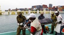 Rescuers carry the recovered body of a passenger killed during the ferry tragedy from a boat at the Port of Zanzibar, July 19, 2012. (THOMAS MUKOYA/REUTERS)