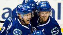 Vancouver Canucks' Henrik Sedin, of Sweden, from left to right, Ryan Kesler and Daniel Sedin, of Sweden, celebrate Henrik's goal against the Columbus Blue Jackets during second period NHL hockey action in Vancouver, B.C., on Friday November 22, 2013. (DARRYL DYCK/THE CANADIAN PRESS)