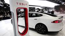 A Tesla S electric car and a charging station are displayed during the press preview day of the North American International Auto Show in Detroit, Michigan January 14, 2014. (REBECCA COOK/REUTERS)