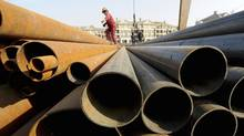 A labourer walks on steel pipes at a steel market in Hefei, Anhui province (JIANAN YU/Jianan Yu/Reuters)