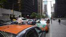 Taxis cue along Wellington St West in downtown Toronto on Sept 13 2013. (Fred Lum/The Globe and Mail)