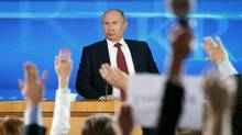 Members of the media raise their hands to ask questions as Russian President Vladimir Putin gives a news conference in Moscow, Dec. 20, 2012. (Misha Japaridze/AP)