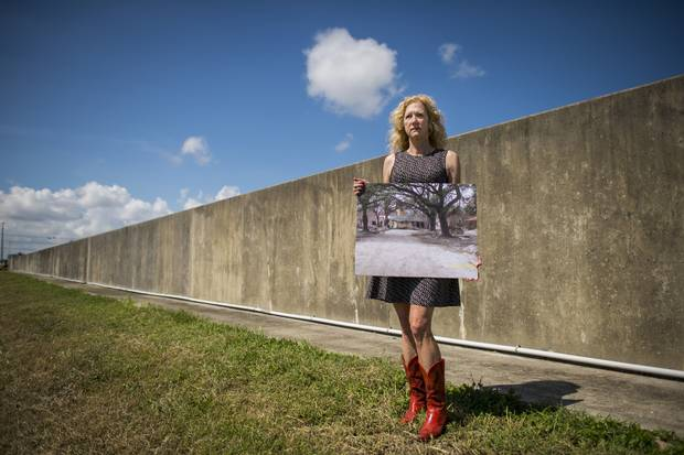 Sandy Rosenthal, founder and executive director of Levees.org, stands next to a levee in New Orleans that failed after Hurricane Katrina in 2005. She holds a photo of the home that was destroyed and moved into the middle of the street during the storm surge.