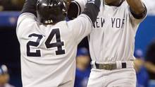 New York Yankees Robinson Cano (L) and Alfonso Soriano high five each other after they both scored against the Toronto Blue Jays in the eighth inning of their American League baseball game in Toronto September 18, 2013. (FRED THORNHILL/REUTERS)