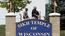 Officials gather near the Sikh Temple in Oak Creek in Wisconsin August 5, 2012 following a mass shooting inside and outside the Sikh Temple. A shooting during Sunday services at a Sikh temple left at least seven people dead, including a gunman, and at least three critically wounded, police and hospital officials said. (Allen Fredrickson/Reuters)
