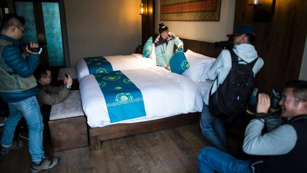 Journalists (L) and government photographers (R) taking pictures of a worker cleaning a bed in a room of the Artel hotel in Lulang, near Nyingchi in China's Tibet Autonomous Region.