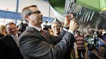 Ontario Premier Dalton McGuinty tries his hand at aircraft assembly during a news conference at a Toronto Bombardier plant on May 29, 2012. (Fred Lum/The Globe and Mail)