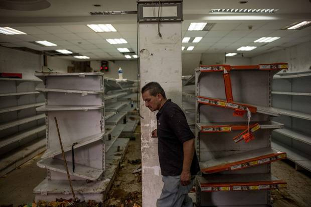 A man walks inside a looted supermarket in El Valle, in west Caracas.