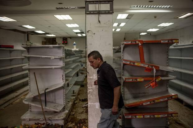 A man walks inside a looted supermarket in El Valle, in west Caracas.