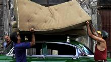 Men load mattresses on a 1954 Chevrolet in Havana in 2010. (Desmond Boylan/Reuters)