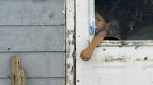 A child reaches through a broken window to open the door of a house on the Pikangikum reserve in Northwest Ontario on Jan. 5, 2007. (John Woods/John Woods/The Canadian Press)