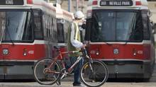 Toronto Transit Commission trams sit idle as a cyclist walk past on the first full day of a public transit strike in Toronto, Saturday April 26, 2008. In response, McGuinty recalled the legislature for a rare Sunday afternoon sitting in hopes of sparing commuter misery for the 1.5-million people who use Toronto's public transit workdays. (Adrian Wyld/The Canadian Press/Adrian Wyld/The Canadian Press)