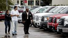 Salesman Kevin Davis, right, walks with customers Tory Borek, center, and Laura Nordin past Ford pick-up trucks on the dealership lot at Capital Ford in Raleigh, North Carolina, U.S., in this file photo. (Jim R. Bounds/Bloomberg)