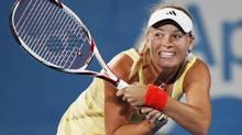 Caroline Wozniacki of Denmark hits a return to Agnieszka Radwanska of Poland during their match at the Sydney International tennis tournament. (DANIEL MUNOZ/Reuters)