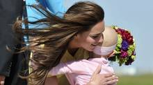 Catherine, the Duchess of Cambridge is presented with flowers and a hug by 6-year-old Diamond Marshall on arrival with Prince William at Calgary International Airport in Calgary on July 7, 2011. (TODD KOROL/AFP/Getty Images)