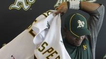 Oakland Athletics' Yoenis Cespedes, a defector from Cuba, puts on his jersey during a news conference at baseball spring training, Sunday, March 4, 2012, in Phoenix. (AP Photo/Darron Cummings) (Darron Cummings/AP)