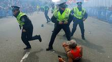 Runner Bill Iffrig, 78, lies on the ground as police officers react to a second explosion at the finish line of the Boston Marathon, April 15, 2013. (John Tlumacki/The Boston Globe/AP)