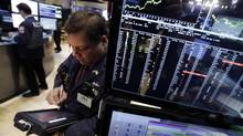 Trader John Santiago works on the floor of the New York Stock Exchange Monday, Jan. 27, 2014. (Richard Drew/AP)
