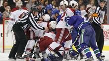 Officials try to restore order as members of the Vancouver Canucks and Phoenix Coyotes fight during first period NHL action in Vancouver. (Darryl Dyck/The Canadian Press)