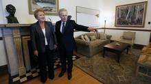 Former Quebec Premier Jean Charest (R) speaks with new Premier-Designate Pauline Marois during a photo-op at his office at the National Assembly in Quebec City, September 6, 2012. (MATHIEU BELANGER/REUTERS)