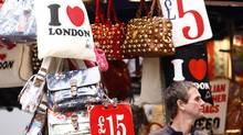 A market stall holder stands under bags with different prices on Oxford Street, London. (ANDREW WINNING/REUTERS)