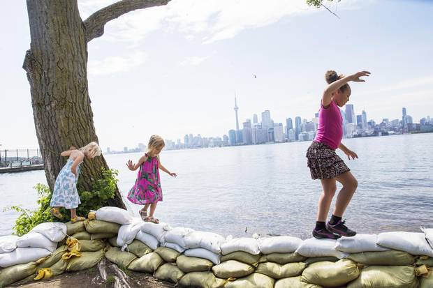 Twin sisters Izzy and Billie Page and their schoolmate Ireal Similien, 9, play on the sand bags on Ward's Island on Wednesday.