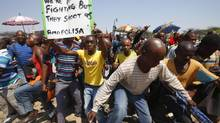 Striking platinum miners march near the Anglo-American Platinum (Amplats) mine near Rustenburg in South Africa on Oct. 12, 2012. (MIKE HUTCHINGS/REUTERS)