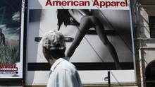 People passing near Yonge and Gould streets look up at an American Apparel store billboard in Toronto. (Deborah Baic/The Globe and Mail)