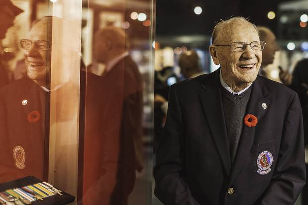 Johnny Bower looks over vintage memorabilia during the opening of an exhibition on hockey and the First World War held at the Hockey Hall of Fame in 2014.