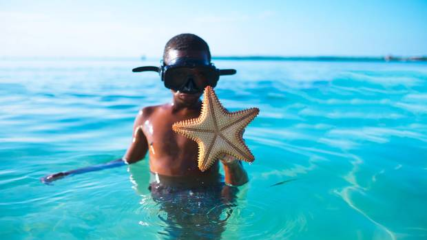 A boy displays a starfish he's caught snorkelling by Caye Caulker.