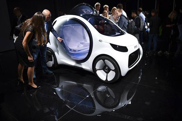 Visitors stand next to a Smart 'Vision EQ' on the first press day of the Frankfurt International Motor Show IAA in Frankfurt, Germany, Tuesday, Sept. 12, 2017.