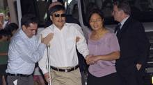 Blind Chinese dissident Chen Guangcheng (centre) is helped by his wife Yuan Weijing (right) after arriving in New York May 19, 2012. (KEITH BEDFORD/REUTERS)