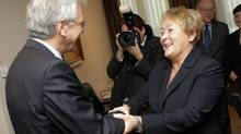 Quebec Premier Pauline Marois, right, is welcomed by Flanders Minister-President Kris Peeters at his office in Brussels on Dec. 16, 2013. (YVES LOGGHE/ASSOCIATED PRESS)