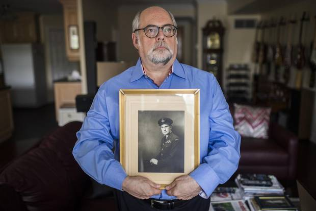 Marc Stevens poses for holding a portrait of his father Peter Stevens, in Toronto, Friday August 4, 2017. Peter Stevens was British air force that was in fact a German-born Jew named Georg Hein, but his mother had sent him to England ahead of the Nazi takeover.