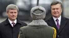 Prime Minister Stephen Harper and Ukrainian President Viktor Yanukovych inspect troops during a welcoming ceremony in Kiev on Oct. 25, 2010. (Sergei Chuzavkov/AP)