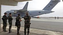 French soldiers look at a Canadian Air Force C-17 transport plane which carries French army equipment at the airport in Bamako January 22, 2013. (ERIC GAILLARD/REUTERS)