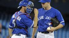 Toronto Blue Jays catcher J.P. Arencibia (L) talks to pitcher J.A. Happ after walking the bases loaded against the Oakland Athletics during the seventh inning of their MLB American League baseball game in Toronto July 24, 2012. (Mike Cassese/REUTERS)