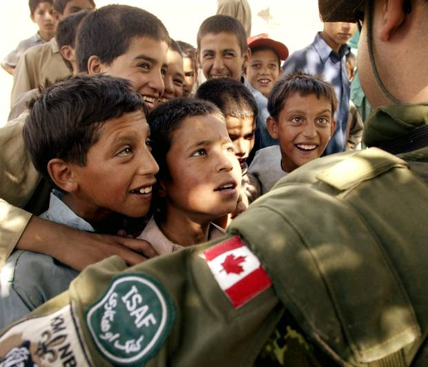 A Canadian corporal is surrounded by curious Afghan children as he and Canadian military engineers tour local villages around their base camp in Kabul Afghanistan, on Aug. 18, 2003.